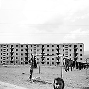 A lady hangs out the washing as children play in a housing estate surrounded by unfinished communist style housing blocks which still stand in the heart of the housing estate of the small Romanian town of  Copsa Mica, Transylvania, Romania. Copsa Mica was once described as the most polluted town in Europe. May 9, 2008. Photo Tim Clayton....Copsa Mica, a small industrial town deep in Transylvania, Romania, was described during the 1990s as the most polluted town in Europe with lead levels reaching were more than 1000 times the allowable International limits and life expectancy nine years shorter than the National average...The pollution was caused entirely by two factories, Carbosin produced black for dies and tires and closed in 1993 while Sometra, a nonferrous smelter is still operational today...The pollution was so bad sheep were black, covered in soot and health officials advised against eating livestock or vegetables and drinking the water or milk...The Communist rule of Nicolae Ceausescu is blamed for the widespread environmental degradation that left industrial parts of Romania in ecological disaster. Industry was situated in a way to concentrate pollution in small areas leaving the rest of the country relatively free of pollution. Copsa Mica in particular was left an environmental disaster...The pollution caused a direct affect on human health with widespread Lung disease, Impotency, the highest infant mortality rate in Europe, Lead poisoning and behavioral problems...Fifteen years on since the closure of Carbosin in 1993, the factory skeleton remains as part of the towns bleak landscape, Unfinished communist style housing blocks still stand in the heart of the towns housing estate. The town's inhabitants are still trying to recover from the long lasting effects of pollution...Recent survey's found the soil contained so much lead that it was 92 times above the permitted level; the vegetation had a lead content 22 times above the permitted l