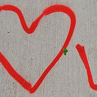 Red Love You graffiti on a New York City sidewalk.