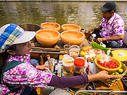 12 FEBRUARY 2015 - BANGKOK, THAILAND: A vendor makes som-tam, or Thai spicy papaya salad, in her canoe in the floating market opened on Khlong Phadung Krung Kasem, a 5.5 kilometre long canal dug as a moat around Bangkok in the 1850s. The floating market opened at the north end of the canal near Government House, which is the office of the Prime Minister. The floating market was the idea of Thai Prime Minister General Prayuth Chan-ocha. The market will be open until March 1.    PHOTO BY JACK KURTZ