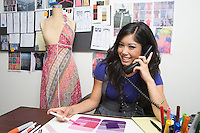Portrait of female fashion designer using telephone at desk