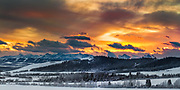 Mountain sunset viewed from the Alberta Foothills.  The bright orange sky contrasts with the snow covered fields and mountains and results in a dramatic ending to the year.  New Years Eve 2013-2014