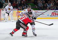 KELOWNA, CANADA - OCTOBER 4:  Henrik Nyberg #21 of the Kelowna Rockets checks Nic Petan #19 of the Portland Winterhawks  at the Kelowna Rockets on October 4, 2013 at Prospera Place in Kelowna, British Columbia, Canada (Photo by Marissa Baecker/Shoot the Breeze) *** Local Caption ***