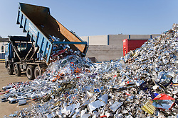 Tipper lorry shedding its load of discarded tin cans from factories into a pile at the metal recycling centre ready for sorting and baling,