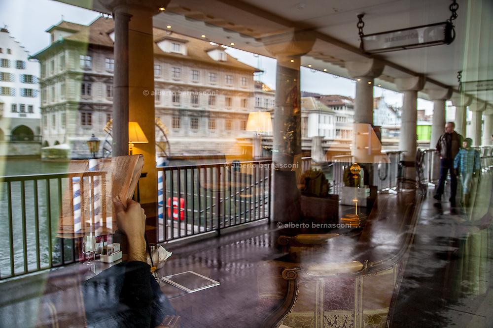 Switzerland, Zurich: hotel hall along the river. man reading newspaper