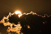 Sun setting into dark clouds