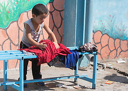 """© Licensed to Alison Baskerville. 14/07/2014. Gaza.   A young Palestinian boy helps with the laundry on a UN school now being used by over 600 people who have evacuated their homes from the north of Gaza.  Many left with limited supplies.  With no sign of the crisis ending the school is now concerned that they will run out of water and supplies.  """"I don't know how much longer we will be able to go on in this situation.""""  Commented Abdil Sawan, the UN representative within the school.  Photo credit : Alison Baskerville/LNP"""