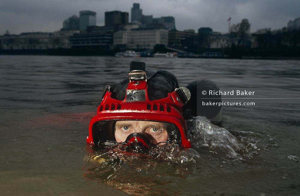 A Metropolitan Police diver surfaces beneath the murky waters of the River Thames in front of the tall buildings of the City of London, England. Blowing bubbles, he exhales through his oxygenated mask and looks through the Plexiglass to the viewer. The Underwater and Confined Space Search Team (UCSST), are part of the Marine Support Unit and based at Wapping. They also carry out searches in canals, ponds, lakes and reservoirs. It was set up as a full time unit in 1964. One of their most distressing jobs, however, is recovering bodies from the River. On average over 50 people lose their lives in the Thames each year and about 80% of these are by suicide (usually by jumping off one of the many bridges that cross the Thames). After a body is recovered from the River it is taken to the mortuary at Wapping Police Station for identification.