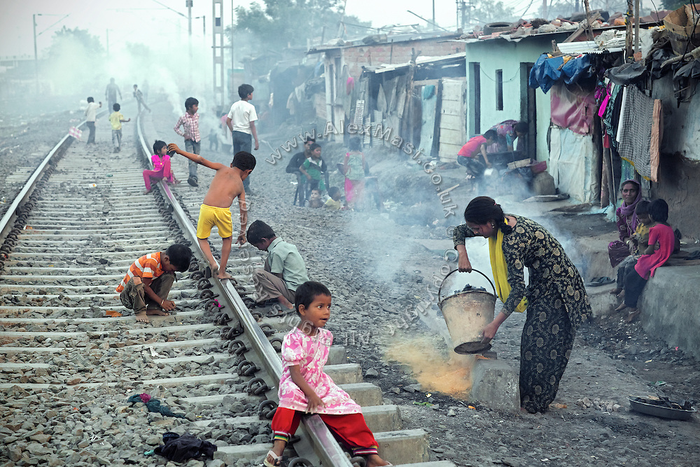 In the afternoon, children are playing around while women are going about their daily routine, in front of their modest homes along the railway tracks in New Arif Nagar, one of the water-affected colonies standing next to the abandoned Union Carbide (now DOW Chemical) industrial complex, site of the infamous 1984 gas tragedy in Bhopal, Madhya Pradesh, central India. The poisonous cloud that enveloped Bhopal left everlasting consequences that today continue to consume people's lives.