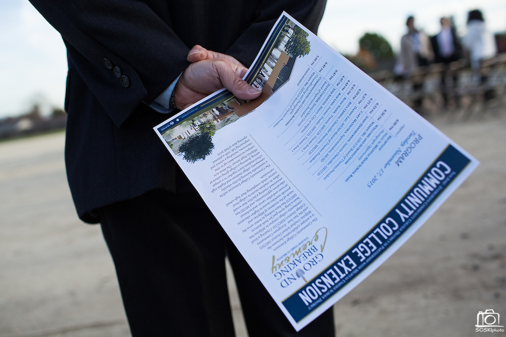 A guest holds an informational flier during the Milpitas Unified School District and San Jose Evergreen Community College District Community College Extension Ground Breaking Ceremony near Russell Middle School in Milpitas, California, on November 17, 2015. (Stan Olszewski/SOSKIphoto)