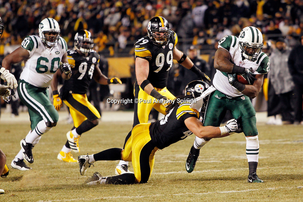 New York Jets running back Shonn Greene (23) gets tackled by Pittsburgh Steelers safety Troy Polamalu (43) in the fourth quarter of the NFL 2011 AFC Championship playoff football game on Sunday, January 23, 2011 in Pittsburgh, Pennsylvania. The Steelers won the game 24-19. (©Paul Anthony Spinelli)