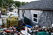 Lobster traps, ropes and floats piled up next to a boat house in the lobster fishing community of New Harbor, Maine. The tiny picturesque pocket harbor is one of the last working harbors on the midcoast along the Pemaquid Peninsula