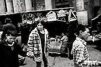 Carmen de Mata walks with her sons through a market along the central plaza after Mass. de Mata looks foward to moving into a place that rents rooms. One room is enough for us since we don't have a lot of things, she says.