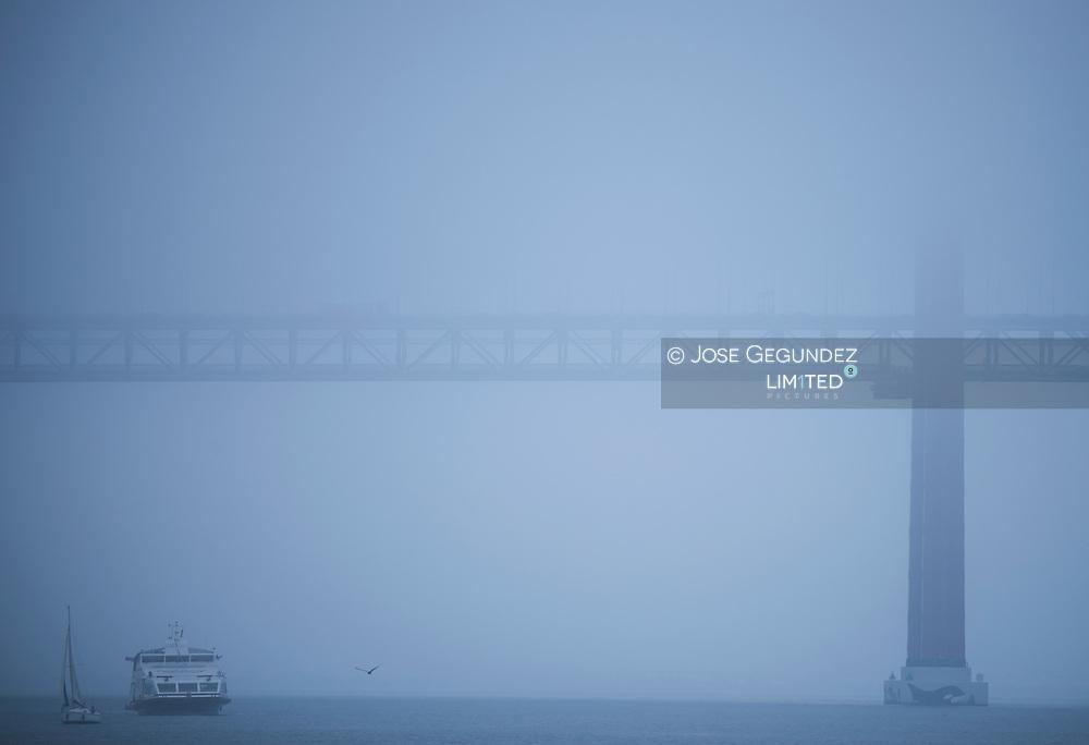 Boats at mystic fog on 25 Abril bridge in Lisbon, Portugal