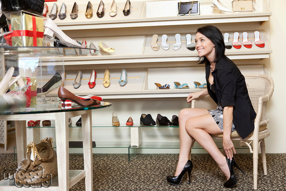 Happy mid adult woman trying high heels in footwear store