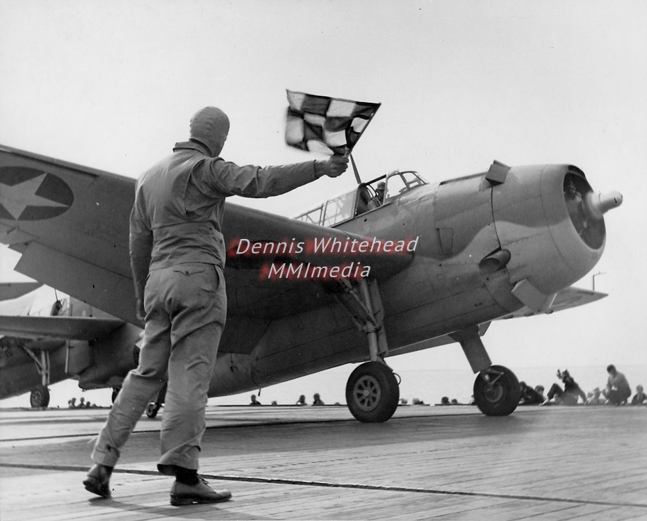 The dispatching officer waves on a U.S. Navy Torpedo Bomber Fighter (TBF) on the flight deck of the USS Santee.