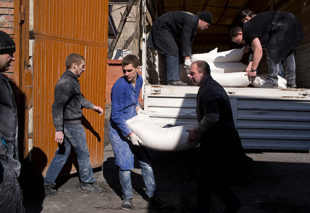 Mine workers unload sugar and flour from a humanitarian aid convoy from Russia at Zasyadtko Mine on March 7, 2015 in Donetsk, Ukraine.