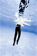 Underwater view of a woman fully clothed floating, head above the water. Tonga