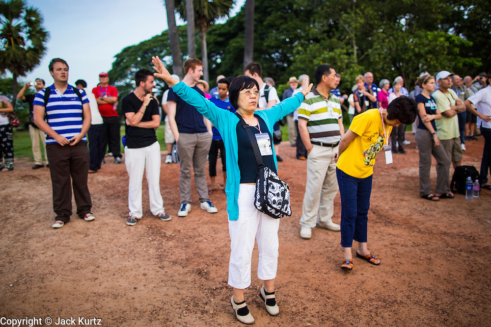 "02 JULY 2013 - ANGKOR WAT, SIEM REAP, SIEM REAP, CAMBODIA:  A tourist does tai-chi exercises while she waits for the sunrise at Angkor Wat. Angkor Wat is the largest temple complex in the world. The temple was built by the Khmer King Suryavarman II in the early 12th century in Yasodharapura (present-day Angkor), the capital of the Khmer Empire, as his state temple and eventual mausoleum. Angkor Wat was dedicated to Vishnu. It is the best-preserved temple at the site, and has remained a religious centre since its foundation – first Hindu, then Buddhist. The temple is at the top of the high classical style of Khmer architecture. It is a symbol of Cambodia, appearing on the national flag, and it is the country's prime attraction for visitors. The temple is admired for the architecture, the extensive bas-reliefs, and for the numerous devatas adorning its walls. The modern name, Angkor Wat, means ""Temple City"" or ""City of Temples"" in Khmer; Angkor, meaning ""city"" or ""capital city"", is a vernacular form of the word nokor, which comes from the Sanskrit word nagara. Wat is the Khmer word for ""temple grounds"", derived from the Pali word ""vatta."" Prior to this time the temple was known as Preah Pisnulok, after the posthumous title of its founder. It is also the name of complex of temples, which includes Bayon and Preah Khan, in the vicinity. It is by far the most visited tourist attraction in Cambodia. More than half of all tourists to Cambodia visit Angkor.         PHOTO BY JACK KURTZ"