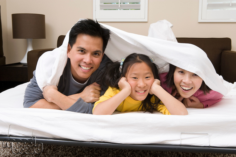 Mother, father and daughter lying down on bed covered with bed sheet