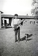 teenaged boy holding a hunting gun with dog on a farm yard
