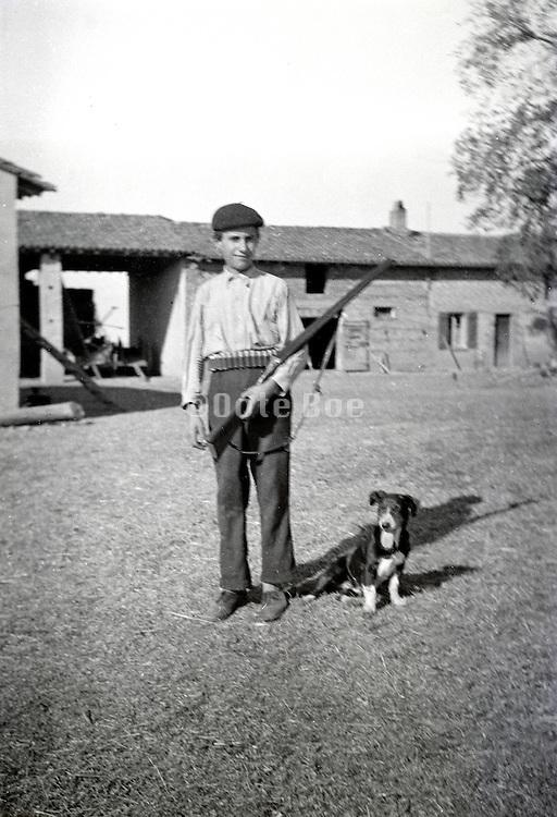 teenaged boy holding a hunting gun with dog on a farm yard