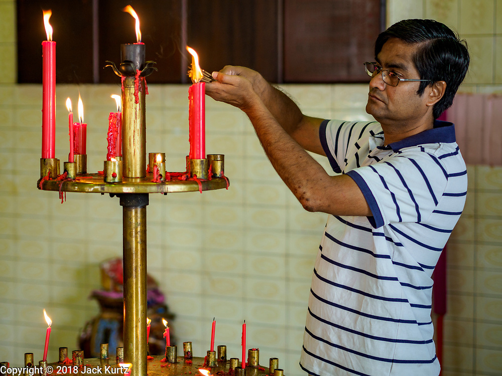 25 AUGUST 2018 - GEORGE TOWN, PENANG, MALAYSIA: A man lights candles to pray in Yap Kongsi Temple on Ghost Day, the full moon day (or night) that falls in the middle of Hungry Ghost month. The Ghost Festival, also known as the Hungry Ghost Festival is a traditional Taoist and Buddhist festival held in Chinese communities throughout Asia. Ghost Day, is on the 15th night of the seventh month (25 August in 2018). During Ghost Festival, the deceased are believed to visit the living. In many Chinese communities, there are Chinese operas and puppet shows and elaborate banquets are staged to appease the ghosts.      PHOTO BY JACK KURTZ