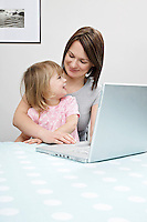Mother and daughter (3-4) sitting beside laptop