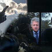 July 14, 2006 - President Clinton, seen through the window of a car, with a supporter's reflection in the glass, stops on the side of the road in Malawi to greet throngs of well wishers and to answer reporters questions. Clinton met with Malawi's President, Bingu Wa Mutharika, and signed an agreement to launch the Clinton Hunter Development Initiative. Photo by Evelyn Hockstein