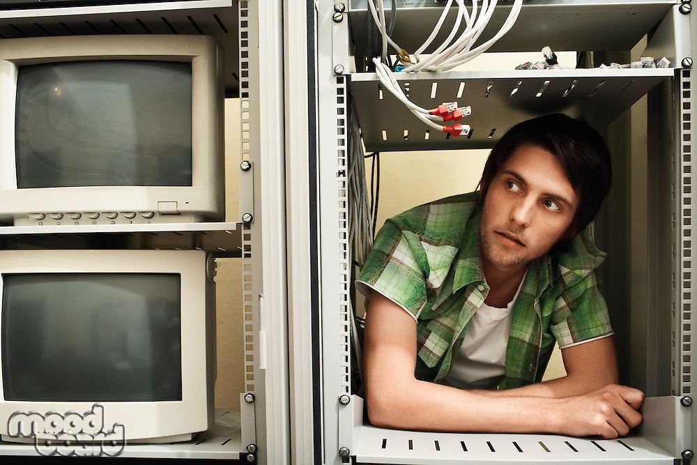 Young man surrounded by computer equipment.