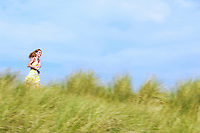 Young Woman Running through Tall Grass in meadow