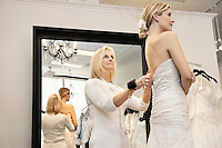 Senior owner assisting young bride getting dressed in wedding gown
