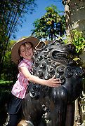 Child (6 years old) playing on one of two bronze lions, known as Temple Dogs, in Royal Botanic Gardens. Sydney, Australia