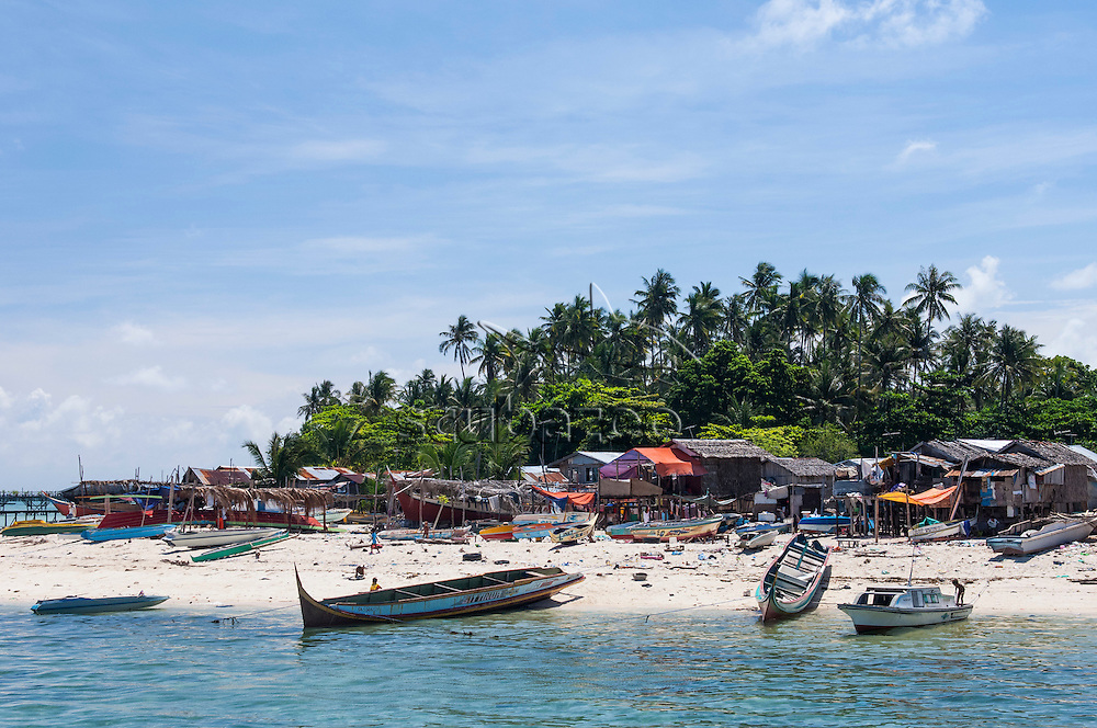 A Bajau sea gypsy village on the beach with palm trees in the background, Mabul Island, Sabah, Malaysia.
