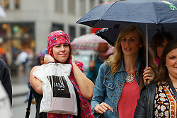 © Licensed to London News Pictures. 19/08/2016. London, UK. Shoppers take shelter from the rain on Oxford Street in London on 19 August 2016. Photo credit: Tolga Akmen/LNP