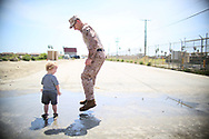 Staff Sgt William Proctor plays in a mud puddle with his son Elijah during a homecoming reception at Camp Pendleton on Thursday, May 11, 2017 in Oceanside, California.   Marines and sailors from the 11th Marine Expeditionary Unit returned to Camp Pendleton after serving seven months in the Western Pacific, Middle East, and Horn of Africa.