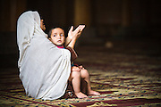 Kashmir. A woman worships at the mosque with her child.