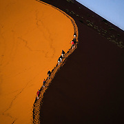 Tourists climb Dune 45 in the early morning at Sossusvlei park. Namibia boasts the world?s oldest and largest sand dunes, extending for 400 miles along the coast and more than 80 miles inland. July 17, 2008. Photo by Evelyn Hockstein for The New York Times.