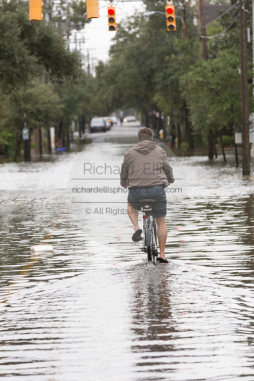 A man rides his bicycle through floodwaters on Rutledge Avenue as severe flooding continued for the second day in the historic district as Hurricane Joaquin brings heavy rain, flooding and strong winds as it passes offshore October 4, 2015 in Charleston, South Carolina.