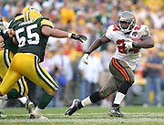 "GREEN BAY, WI - SEPTEMBER 25:  Rookie running back Carnell ""Cadillac"" Williams #24 of the Tampa Bay Buccaneers runs the ball (for a few of his 158 yards in the game) while chased by linebacker Robert Thomas #55 of the Green Bay Packers at Lambeau Field on September 25, 2005 in Green Bay, Wisconsin. The Buccaneers defeated the Packers 17-16. ©Paul Anthony Spinelli *** Local Caption *** Carnell Williams;Robert Thomas"