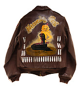 "This is a type A-2 flight jacket that was worn by a member of the 571st squadron. On the front of the jacket is the insignia for the 571st squadron, a wolf dressed in uniform gripping a bomb. The artwork on the back says ""Heavenly Cent"" and includes a lady in black clothing sitting on her knees. Each bomb that is painted on the back signifies a completed mission."
