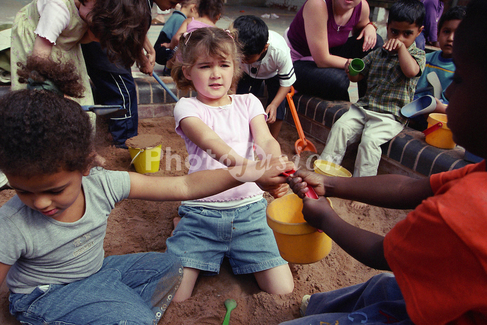 Multiracial group of nursery school children fighting over bucket in playground sandpit,