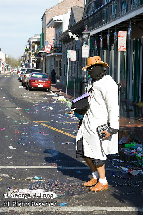 Classic street theatre early on Mardi Gras in the French Quarter as this mysterious man acts like a drunk.
