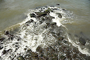 rock being pound by a wave from a boat wake
