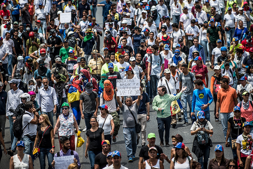 """CARACAS, VENEZUELA - May 24, 2017: A man holds a sign that says, in Spanish: """"Maduro, No one likes you!!! Leave already!""""  The streets of Caracas and other cities across Venezuela have been filled with tens of thousands of demonstrators for nearly 100 days of massive protests, held since April 1st. Protesters are enraged at the government for becoming an increasingly repressive, authoritarian regime that has delayed elections, used armed government loyalist to threaten dissidents, called for the Constitution to be re-written to favor them, jailed and tortured protesters and members of the political opposition, and whose corruption and failed economic policy has caused the current economic crisis that has led to widespread food and medicine shortages across the country.  Independent local media report nearly 100 people have been killed during protests and protest-related riots and looting.  The government currently only officially reports 75 deaths.  Over 2,000 people have been injured, and over 3,000 protesters have been detained by authorities.  PHOTO: Meridith Kohut"""