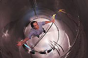 Johnson-Turnbull Winery in Oakville, Napa Valley, California.  Winemaker, Kristin Belair, inside a clean stainless steel fermentation tank. [Once the grapes are harvested, they are poured into a crusher that separates the stems from the grapes; the grapes and juice are then funneled directly into the stainless steel tank for fermentation.]  The winery was purchased in 1992 by Patrick O'Dell and renamed Turnbull Winery. Photographed in 1990. Photographed in 1990. MODEL RELEASED.