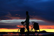 A long distance cyclist enjoys sunset over Lago Titicaca - Bolivia - South America