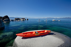 """""""Kayak on a Tahoe Boulder 2"""" - This tandem kayak parked on a boulder was photographed near Speedboat Beach, Lake Tahoe. Two stand up paddle boarders can be seen in the distance."""