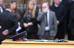 © Licensed to London News Pictures. 22/03/2016. Belfast, Northern Ireland, UK. The hat and gloves of murdered prison officer Adrian Ismay as his coffin leaves Woodvale Methodist church. Mr Ismay died following a booby-trap bomb that exploded under his van in East Belfast on March 4th. Photo credit: Peter Morrison/LNP