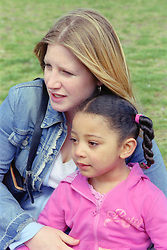 Single mother sitting on grass in playground with young daughter,