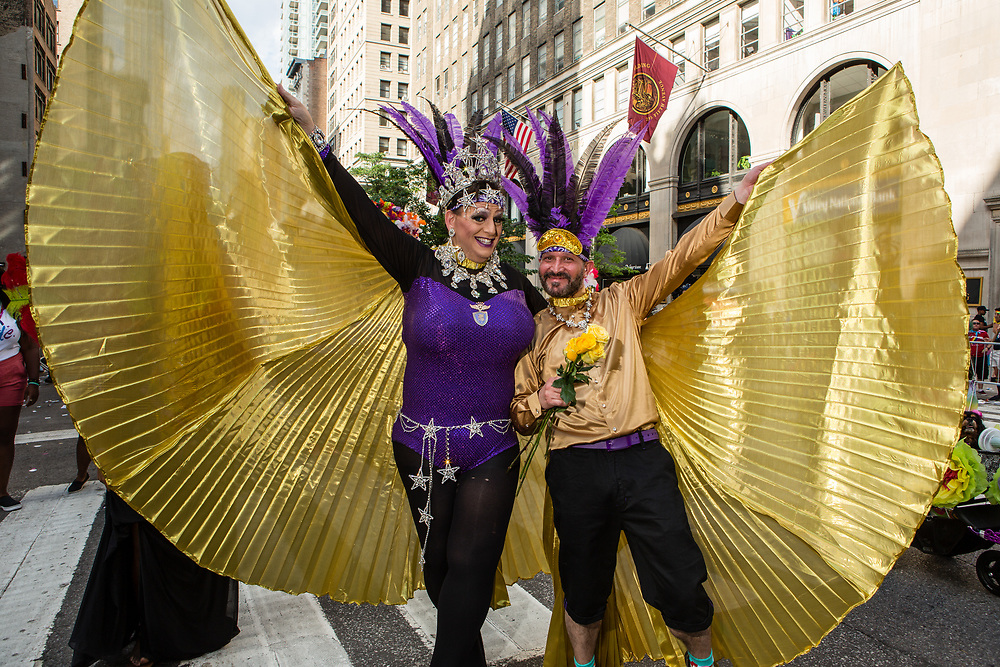 New York, NY - 25 June 2017. New York City Heritage of Pride March filled Fifth Avenue for hours with groups from the LGBT community and it's supporters. Two marchers in colorful costumes and gilt capes.